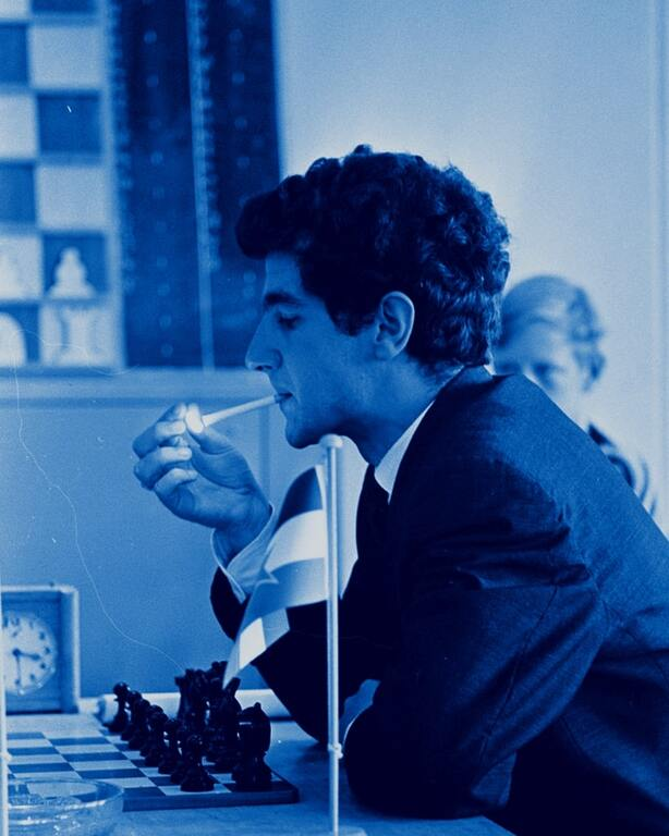 Bruno Parma smoking at chess game with yogoslavia flag in foreground