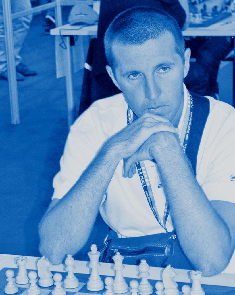 Igralec šaha v ospredju šahovske figurice v modrih barvah